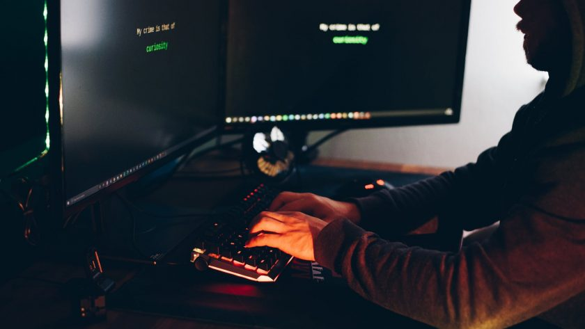 crop hacker silhouette typing on computer keyboard while hacking system