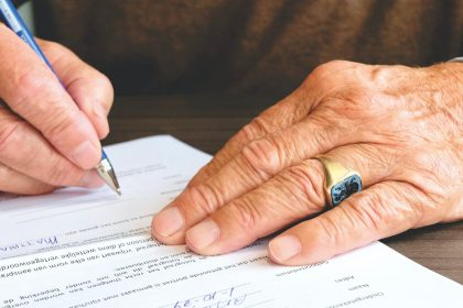 person signing document paper